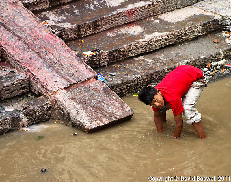 A boy sifts through the mud of the polluted Bagmati River looking for gold and jewelry left from the Hindu cremations that occur on riverside platforms at the Pashupatinath Temple in Kathmandu, Nepal.