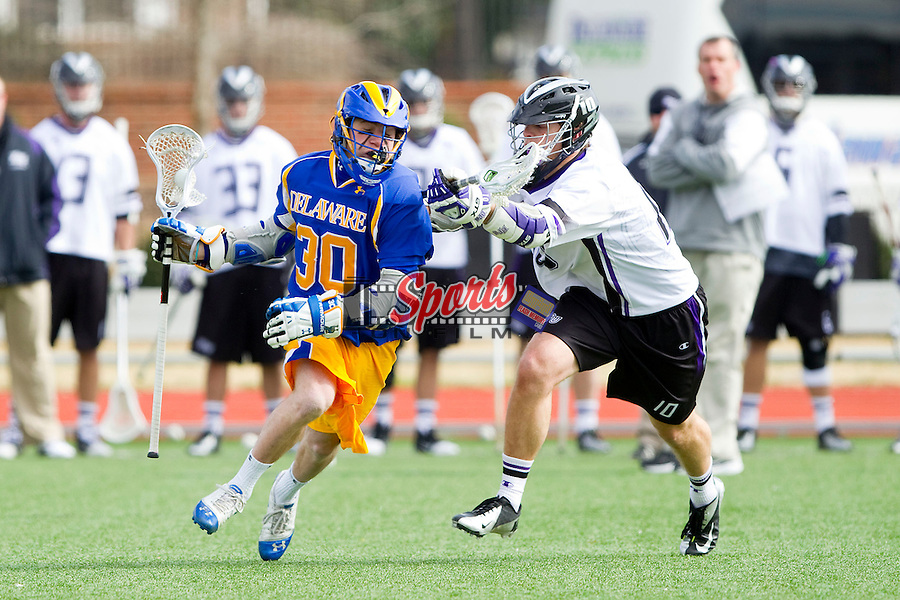 Connor Frisina (30) of the Delaware Blue Hens tries to evade the pursuit of Brad James (10) of the High Point Panthers during first quarter action at Vert Track, Soccer & Lacrosse Stadium on February 2, 2013 in High Point, North Carolina.  The Blue Hens defeated the Panthers 12-10.   (Brian Westerholt/Sports On Film)