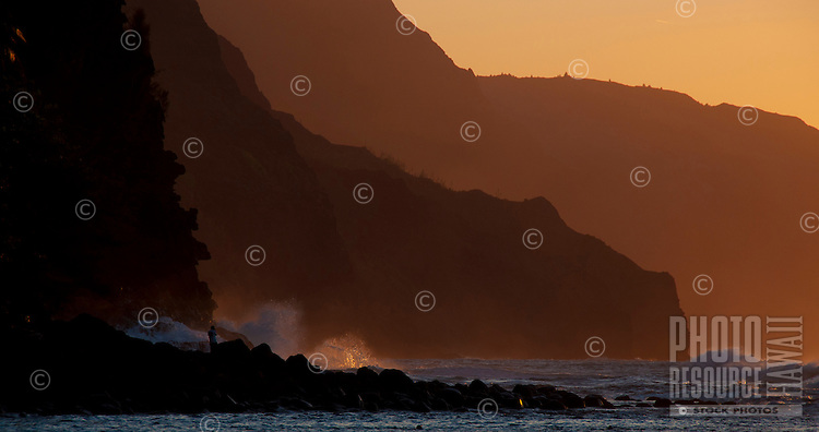 The setting sun lighting up a spectacular splash at the foot of Na Pali near Ke'e Beach, Kauai.