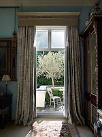 The drawing room French windows lead to a secluded town garden with a paved patio seating area. The curtains are in Hardwick Green by Robert Kime for Chelsea Textiles