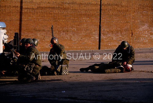 Moscow, Russia.October 4, 1993..Russian soldiers, near the US Embassy attempt to help a seriously wounded soldier after he was hit by an anti-Yeltsin sniper held up in the Parliament building.