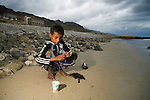 Boy hooking worm for fishing, Hawf Protected Area, Yemen