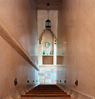 The staircase with tadelakt walls and terracotta tiled steps descends steeply to the entrance hall