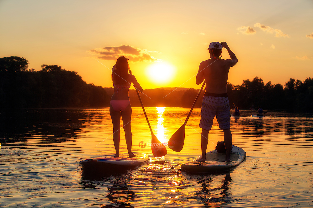 A silhouette of a young couple on a stand-up paddle boards SUP during a beautiful evening sunset on Lady Bird Lake in downtown, Austin, Texas.