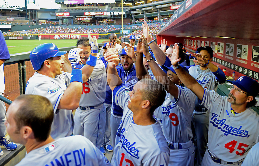 May 21, 2012; Phoenix, AZ, USA; Los Angeles Dodgers catcher Matt Treanor (left) is congratulated by teammates in the dugout after hitting a two run home run in the second inning against the Los Angeles Dodgers at Chase Field.  Mandatory Credit: Mark J. Rebilas-