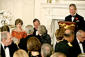 Washington, D.C. - November 2, 2005 -- Charles, Prince of Wales, of Great Britain, right, makes a toast at the start of a Social Dinner in the State Dining Room of the White House in Washington, D.C. on November 2, 2005. The rare black tie dinner was held by President George W. Bush to honor Prince Charles and his wife, Camilla, Duchess of Cornwall, who are on an eight-day visit to the United States. First lady Laura Bush is at the left, and former United States President George H.W. Bush is a approximate center of the photo..Credit: Jay L. Clendenin - Pool via CNP.(Restriction: No New York Metro or other Newspapers within a 75 mile radius of New York City)