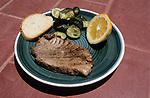ITALY, Sicily, Palermo, plate with freh Tuna fish steak, Zucchini, bread and lemon