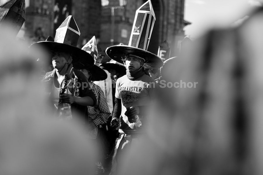 Indians, wearing black cardboard hats, dance during the Inti Raymi (San Juan) festivities in Cotacachi, Ecuador, 24 June 2010. 'La toma de la Plaza' (Taking of the square) is an ancient ritual kept by Andean indigenous communities. From the early morning of the feast day, various groups of San Juan dancers from remote mountain villages dance in a slow trot towards the main square of Cotacachi. Reaching the plaza, Indians start to dance around. They pound in synchronized dance rhythm, shout loudly, whistle and wave whips, showing the strength and aggression. Dancers from either the upper communities (El Topo) or the lower communities (La Calera), joined in respective coalitions, seek to conquer and dominate the square and do not let their rivals enter. If not moderated by the police in time, the high tension between groups always ends up in violent clashes.