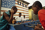 TOWNSHIP LIFE, Ivory Coast. American flag  and kids playing football  game. Yopougon, near Abidjan. West Africa. A  huge  sprawling township across the lagoon from the capital. It has a population of over a million. Yopougon has been the site of numerous massacres, a flash point, problems between Muslims and Christians. Residents are often poor and living in shanties.