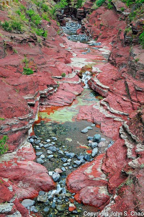 A vertical view of colorful sedimentary mineral layers of green and red argillite, exposed by water erosion over several thousands of years. Red Rock Canyon, Waterton Lakes International Park, Alberta, Canada.