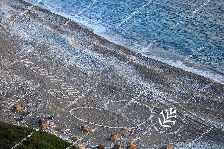 A giant heart shape created with pebbles at Petra Tou Romiou beach seen from above.