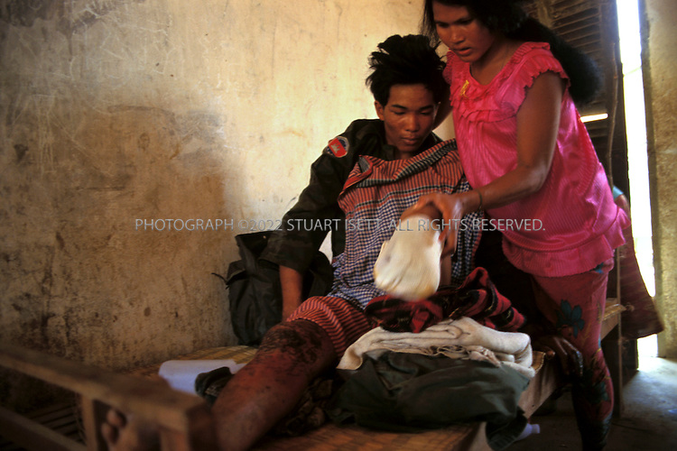 Battambang, Cambodia..A Cambodian government soldier writhes in pain while his wife struggles to keep his amputated leg in place...©2003 Stuart Isett All rights reserved