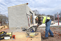 NWA Democrat-Gazette/FLIP PUTTHOFF <br />PEA RIDGE SPLASH PARK<br />Jerrid Gelinas (left) and Nico De Candia work Wednesday Nov. 28 2019 on a splash park being built at Pea Ridge Citiy Park. The splash park will have 20 nozzles, water features and showers, said Rick Campbell with Ellington Contracting. The block building will house pumps and plumbing. The park will be ready to open in the spring.