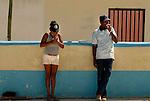 La almendra del cacao se seca al sol en el patio de la iglesia. Hay tres tipos de suelo que cambian su textura y se van usando segun el estado el cacao y el grado de calor.  Aqui una de las trabajadores para de trabajar para encenderse un cigarro mientras un vecino se esta tomando un helado...Chuao. Venezuela. © Juan Naharro