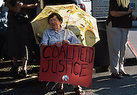 A coalfield resident sits with her sign at a protest rally against mountaintop removal mining.