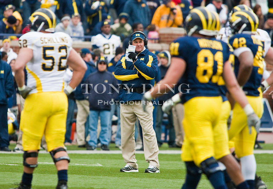 Michigan head coach Rich Rodriguez, center, watches his players on the field during the Wolverines' spring football game, Saturday, April 17, 2010, in Ann Arbor, Mich. (AP Photo/Tony Ding)