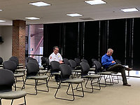 Rogers Deputy Fire Chief William Hyde (left) and Rogers city engineer Lance Jobe (right) attend the Planning Commission meeting Tuesday. Few people attended the meeting, and chairs were spaced out more than usual amid concerns over covid-19. (ALEX GOLDEN/NWA Democrat-Gazette)