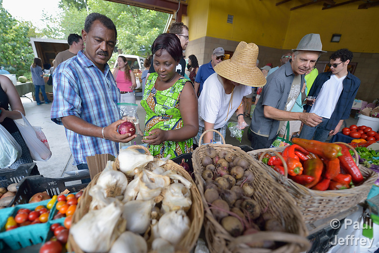 Yosef Birhane, a refugee from Eritrea, and Evanis Gatunzi, a refugee from Rwanda, survey the offerings in the Durham Farmers' Market in Durham, North Carolina. The market's Double Bucks program allows consumers with EBT cards to double their purchasing power.<br /> <br /> Birhane and Gatunzi were resettled in Durham by Church World Service, which resettles refugees in North Carolina and throughout the United States.<br /> <br /> Photo by Paul Jeffrey for Church World Service.