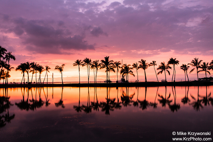 A colorful sunset w/ palm trees reflected by the Waikoloa pond, Big Island, Hawaii