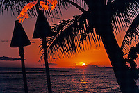 Palm trees and torches are silhouetted against a spectacular orange sunset at Lahaina on Maui.