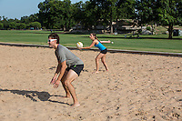 A young attractive female serves volleyball on Zilker Park sand volleyball courts in Austin, Texas.