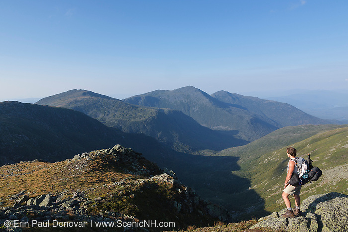 A hiker enjoys the view of the Great Gulf Wilderness from the Appalachian Trail near the summit of Mount Washington in the White Mountains, New Hampshire USA. The Northern Presidential Range is off in the distance.