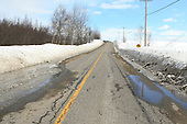 Melting snow in spring leaves large puddles of water along the shoulders of roads