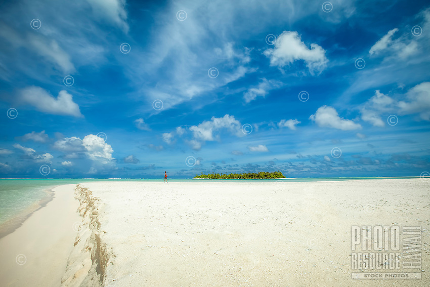 A woman walks on Honeymoon Island beach while looking at the Motu Maina (a.k.a. Maina Island), Aitutaki Lagoon, Aitutaki Atoll, Cook Islands.