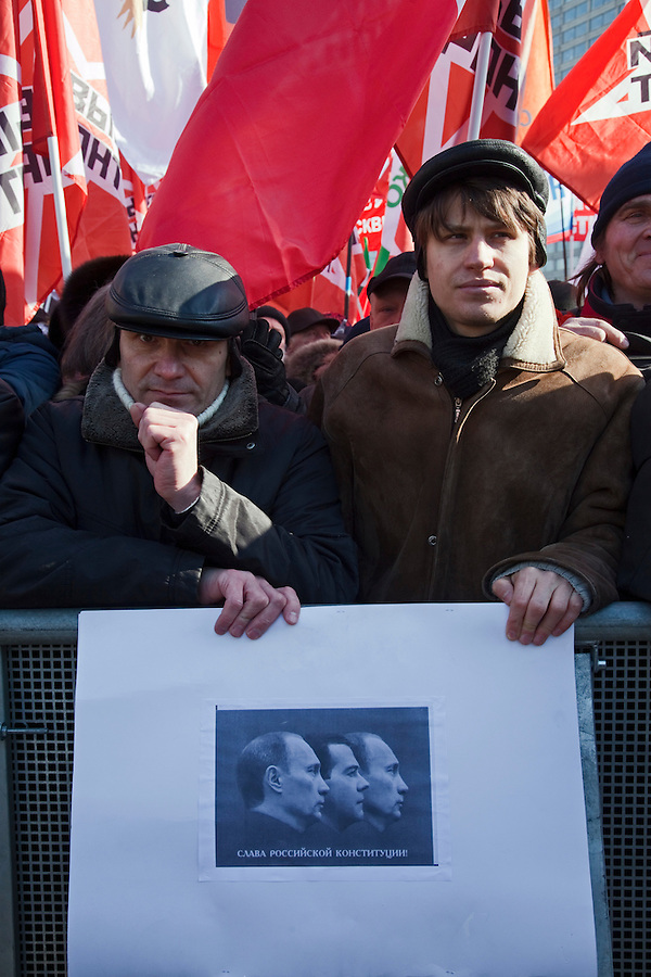 Moscow, Russia, 10/03/2012..Demonstrators hold a poster with images of Putin and Medvedev parodying a Soviet symbol with the words Glory to the Russian Constitution as up to 20,000 people protest in central Moscow against Vladimir Putin's victory in the Russian presidential election.