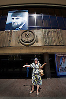 Fatima Davdieva stands in front of the theatre where she used to work as an actress. A large portrait of Chechen president Ramzan Kadyrov now stands above the entrance. Fatima, her husband, and their three children fled Grozny ten years ago during the Second Chechen War as refugees. Now as Belgian nationals they return for the first time to visit their friends, family and former home.