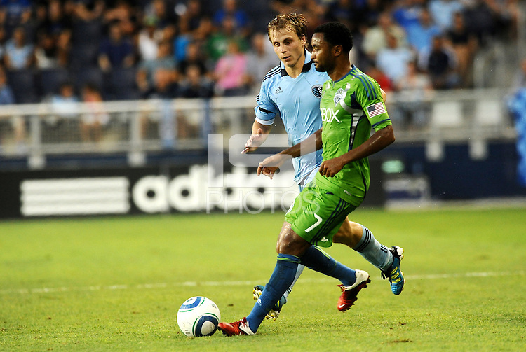 James Riley (7) defender Seattle Sounders watched by Michael Harrington (2) defender Sporting KC... Sporting Kansas City were defeated 1-2 by Seattle Sounders at LIVESTRONG Sporting Park, Kansas City, Kansas.