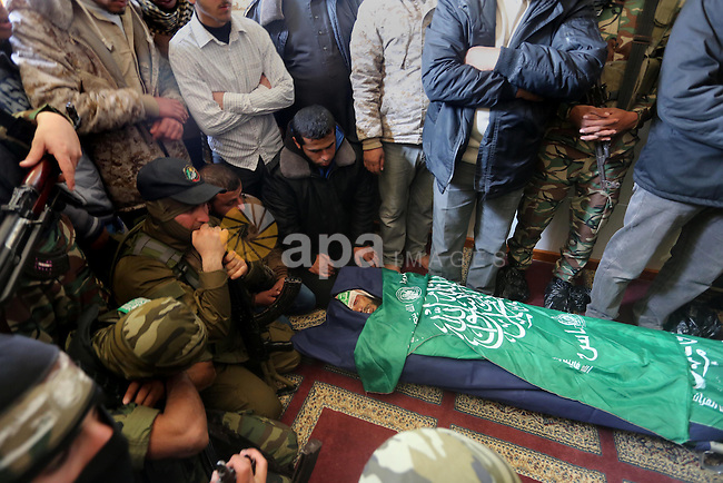 Palestinian militants mourn around the body of Fuad Abu Atewi, who was killed when a tunnel collapse on Tuesday, mourn during his funeral in the village of Al-Moghraga near central Gaza Strip, February 3, 2016. The collapse of a tunnel in the Gaza Strip has killed two militants from Hamas's armed wing, officials said Wednesday, as concern grows in Israel over the rebuilding of tunnels that can be used for attacks. Photo by Mohammed Asad