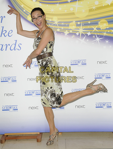 Amanda Donohoe .attends the Life After Stroke Awards at Claridge's Hotel in London, England, UK, June 2nd, 2011..half  length dress white print glasses brown belt grey gray green sleeveless  floral hands gesture funny standing on  one foot leg up arms .CAP/CAN.©Can Nguyen/Capital Pictures.
