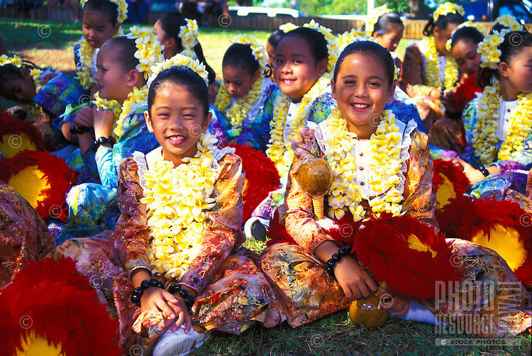 Children with leis and feather rattles uli uli at the annual aloha week parade
