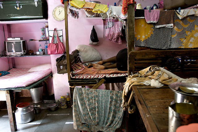 A young sex worker takes a moment to rest with her partner in a family room next to her brothel. Typically one woman or family lives on each bed, and one below.