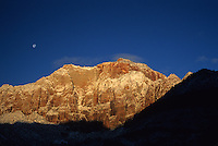 A rising moon looms over snow-dusted canyon walls in Zion National Park, Utah.