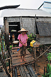 A local women looks in the rain outside of her house made with woods and natural materials that suffer with a leaking water in n Floating Village at one of areas most suffering severe poverty, in Siem Reap, Cambodia. .