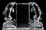 Sculpture of dolphins and a block of ice with ad space illuminated in darkness Isolated silhouete on black background