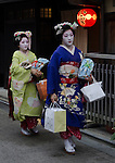 Maiko head to their evening appointments in the Gion district of Kyoto, Japan
