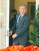 """U.S. President George W. Bush exits the Oval Office before he delivered remarks on the economy in the Rose Garden at the White House in Washington, DC on April 15, 2003.  The White House said in a later release """" As Americans file their income tax returns, the President encouraged Congress to provide the tax relief necessary to grow our economy and create  jobs.  The President has proposed $726 billion in tax relief to create 510,000  new jobs this year and a total of 1.4 million new jobs by the end of next year.  Congress passed a budget ensuring that $550 billion of that amount can pass Congress with a simple majority vote using expedited procedures.  The President will work with Congress to ensure that the final package is at least that size and contains all the elements of his plan so the economy can grow and create as many new jobs as possible.  The President will not be satisfied until everyone looking for work can find it.""""  The President also spoke on the War with Iraq. The President said  """"Our victory in Iraq is certain, but it is not complete.  Centralized power of the dictator has ended  --  yet, in parts of Iraq, desperate and dangerous elements remain.  Forces of our coalition will engage these enemies until they surrender or until they're destroyed.   We have waged this war with determination and with clarity of purpose.  And we will see it through until the job is done.""""<br /> Credit: Ron Sachs / CNP"""