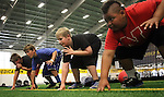 SIOUX FALLS, SD - JULY 2:  Campers, from left, Luke Schuldt,  Charlie Mickelson, Jon Rames, and Titus Benton learn the proper stance during drills at the Riggs Football Academy Tuesday night at the Sanford Fieldhouse. (Photo by Dave Eggen/Inertia)