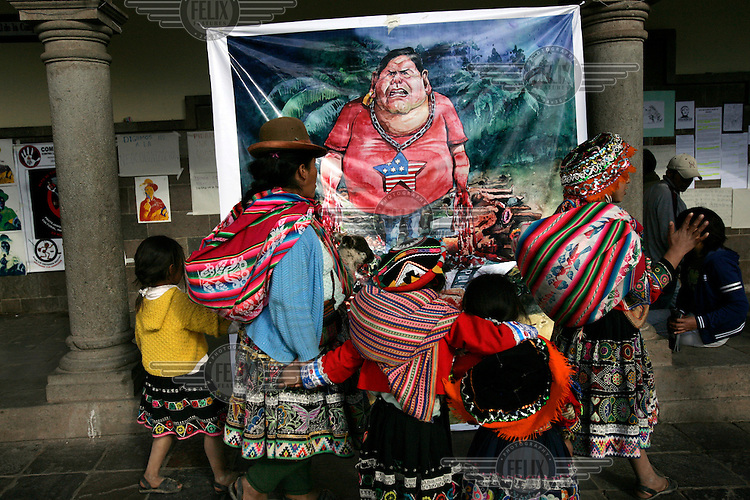 A group of Inca women and children walk past a poster, put up by government protesters, depicting the president Allan Garcia dressed with the American flag and with blood dripping from his hands. ..