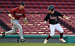 BOSTON, MA - APRIL 17: Harvard's Logan Brano, left, runs down UMass' Nolan Kessinger for an out in the third inning during the 30th Annual Baseball Beanpot Championship Game at Fenway Park in Boston, Massachusetts on April 17, 2019. Photo by Christopher Evans