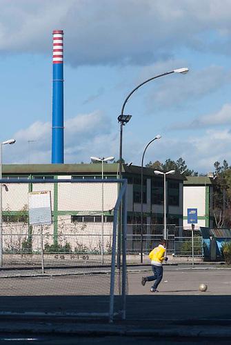 Taranto, Italie, Jan 2010.  La cheminée E312, la plus haute de l'ILVA, vue de Tamburi. Tarente est la ville la plus polluée par émissions industrielles en Europe. A Tarente, chacun des 210 000 habitants respire chaque année 2,7 tonnes de monoxyde de carbone et 57,7 tonnes de dioxydes de carbones. Le quartier ouvrier de Tamburi, tout proche de la zone industrielle souffre très directement de la pollution industrielle. Image issue de la Serie La Poussiere Rouge.