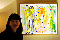 HONG KONG - MARCH 12:  An exhibitor smiles next to the painting 'The view with a view - a blissful world 9' by artistic trio Ma Sing Ling, represented by X-power gallery (Taiwan), displayed as part of the Asia Contemporary Art show that takes place in the bedrooms of Conrad hotel on March 12, 2015 in Hong Kong, Hong Kong.  (Photo by Lucas Schifres/Getty Images)