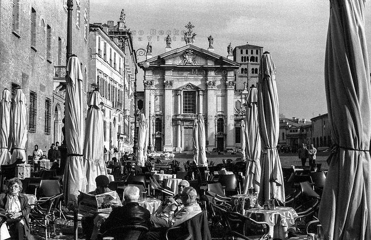 Mantova, piazza Sordello. Gente seduta ai tavolini fuori da un bar e il Duomo sullo sfondo --- Mantua, Sordello square. People sitting outside a bar and the Cathedral on the background