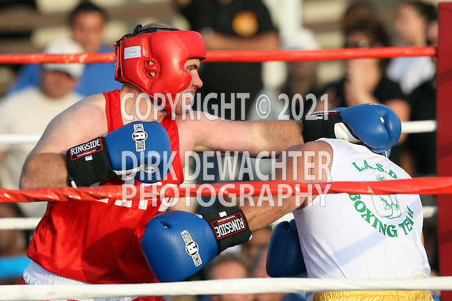 """Whittier, CA 05/10/08 - Eric Nelson of the Los Angeles City Fire Department (in red shirt and red trunks) boxes against Los Angeles County Sheriff's Department's Dave """"Knockout"""" Apodaca during the LASD boxing event held at the Los Angeles County Sheriff's Academy in Whittier."""