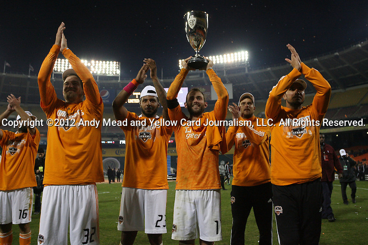 18 November 2012: Houston's Brad Davis (11) holds the Eastern Conference trophy overhead in front of their fans with teammates Adam Moffat (SCO) (16), Bobby Boswell (32), Giles Barnes (ENG) (23), and Brian Ching (right). DC United played the Houston Dynamo at RFK Stadium in Washington, DC in the second leg of their 2012 MLS Cup Playoffs Eastern Conference Final series. The game ended in a 1-1 tie, Houston won the series 4-2 on aggregate goals.