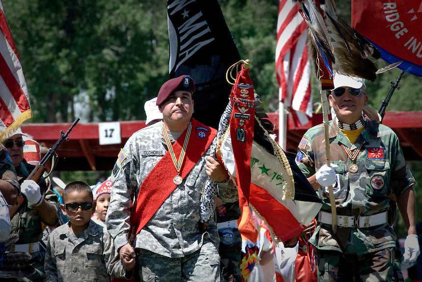 "John Old Horse (R) at the Grand opening of the Veteran?s Powwow in Pine Ridge Indian Reservation. John Old Horse recently came back from Iraq. He is holding a staff made from a sword, an Iraqi flag captured in an assault on an Iraqi police station and a kafea taken from a dead Al Qaeda member. ""When I signed to go to Iraq, it was the Lakota way to be like our ancestors, it was American because I wanted to be like Rambo"" share with laud laughing Jon Old Horse, a third generation Old Horse who went to war to proves his menhood and to become a modern day warrior. He came back from Iraq a different man with  severe PTSD. Jon just earned his bachelor degree in Oglala Lakota studies and received a lakota language certificate. I'm very thankful that my life has turned around and have found peace, shared Jon."