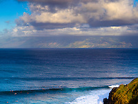 Surfers ride the large waves at Maui's Honolua Bay, with Moloka'i in the distance.
